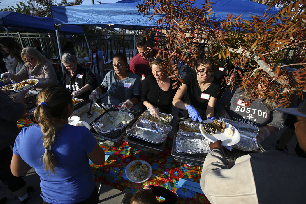 Volunteers serve food to attendees during an annual Thanksgiving outreach event hosted by Casa de Luz and the Las Vegas Metropolitan Police Department's Downtown Area Command at Stupak Park in the ...