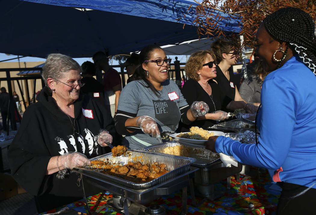 Volunteers Sylvia Buckman, left, and LeAndra Thompson serve food to attendees during an annual Thanksgiving outreach event hosted by Casa de Luz and the Las Vegas Metropolitan Police Department's ...