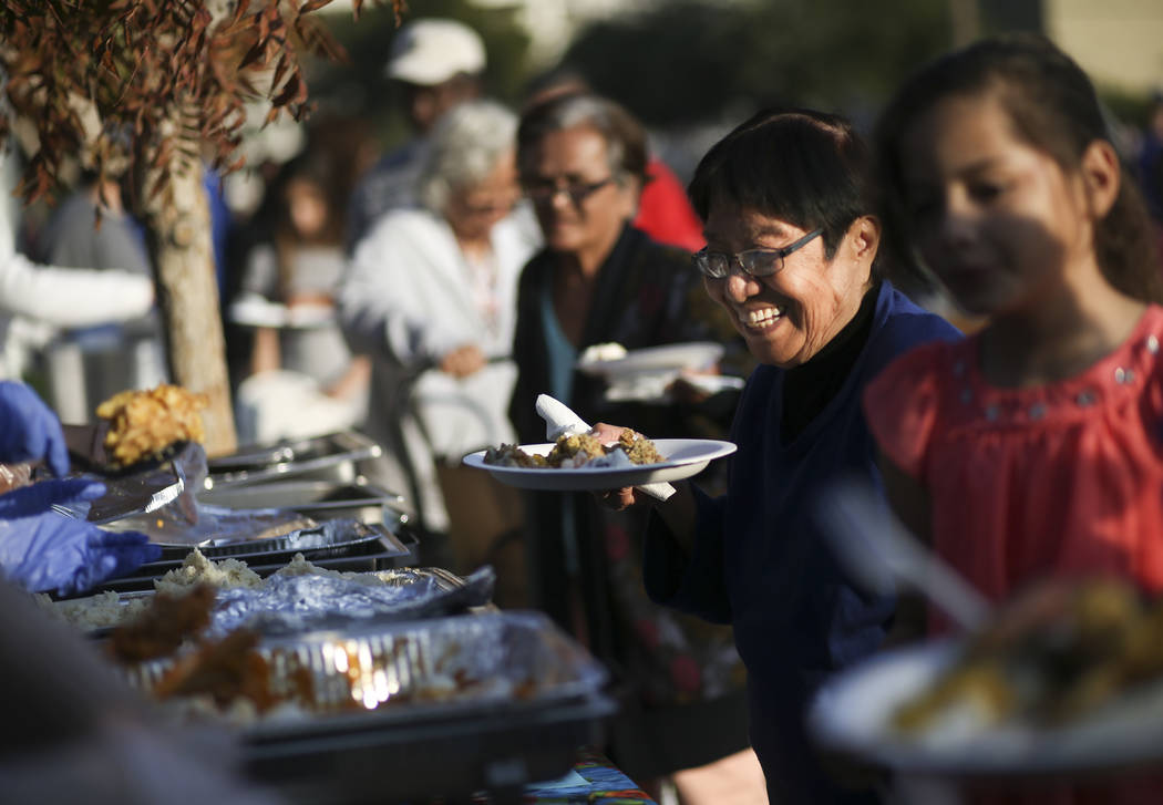 Lourdes Leonen smiles while being served a hot meal during an annual Thanksgiving outreach event hosted by Casa de Luz and the Las Vegas Metropolitan Police Department's Downtown Area Command at S ...