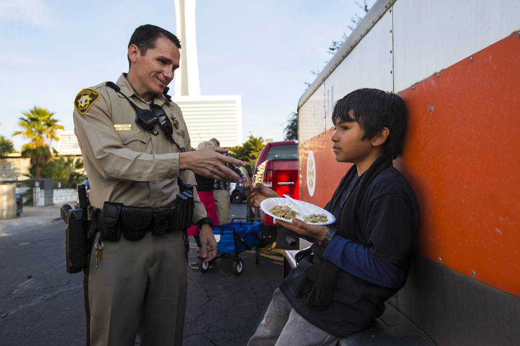 Las Vegas police officer D. Osborne hands a sticker to Jesus Garcia, 10, during an annual Thanksgiving outreach event hosted by Casa de Luz and the Las Vegas Metropolitan Police Department's Downt ...