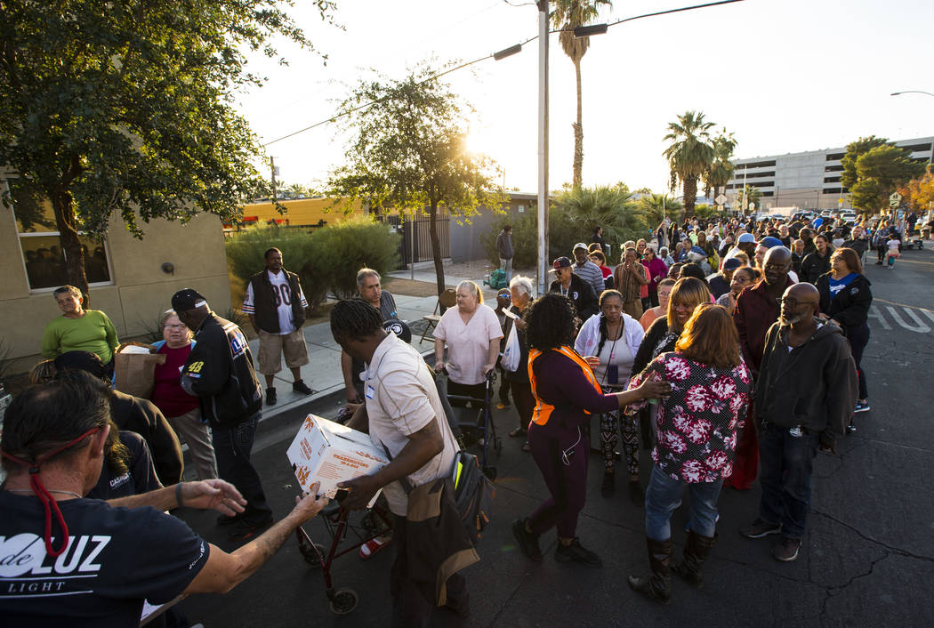 Attendees line up for a boxed Thanksgiving meal during an annual Thanksgiving outreach event hosted by Casa de Luz and the Las Vegas Metropolitan Police Department's Downtown Area Command at Stupa ...