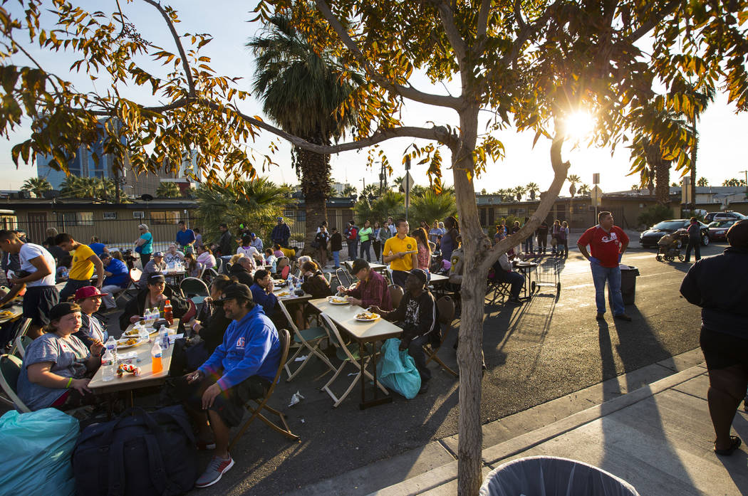 Attendees enjoy a hot meal during an annual Thanksgiving outreach event hosted by Casa de Luz and the Las Vegas Metropolitan Police Department's Downtown Area Command at Stupak Park in the Gateway ...