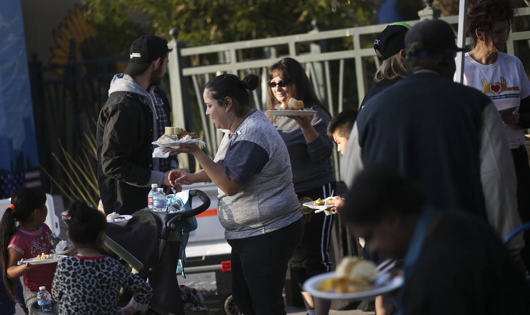 Attendees get plates of food during an annual Thanksgiving outreach event hosted by Casa de Luz and the Las Vegas Metropolitan Police Department's Downtown Area Command at Stupak Park in the Gatew ...