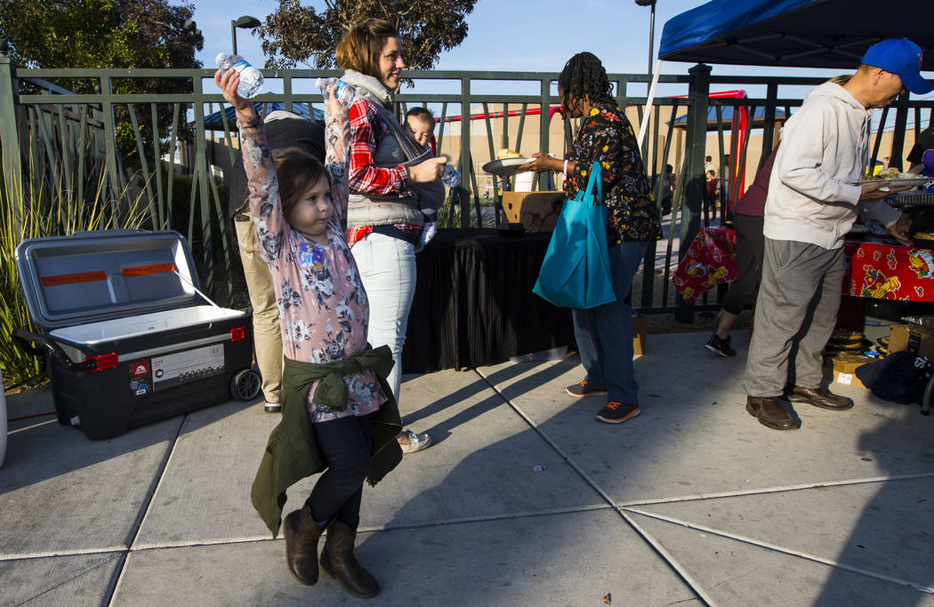 Four-year-old Olive Foster helps hand out water during an annual Thanksgiving outreach event hosted by Casa de Luz and the Las Vegas Metropolitan Police Department's Downtown Area Command at Stupa ...