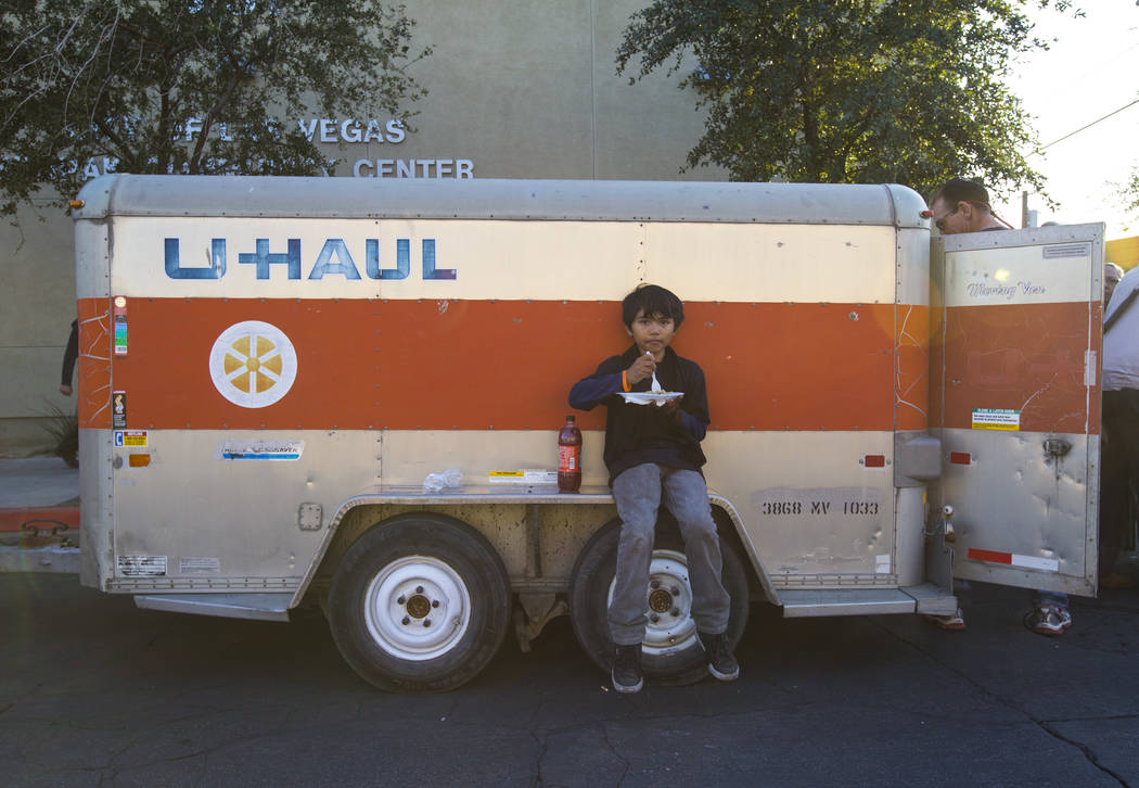 Jesus Garcia, 10, eats during an annual Thanksgiving outreach event hosted by Casa de Luz and the Las Vegas Metropolitan Police Department's Downtown Area Command at Stupak Park in the Gateway nei ...