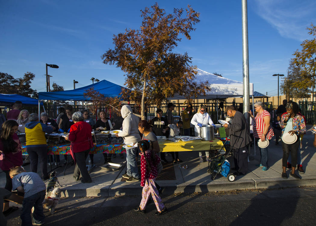 Attendees line up for a hot meal during an annual Thanksgiving outreach event hosted by Casa de Luz and the Las Vegas Metropolitan Police Department's Downtown Area Command at Stupak Park in the G ...