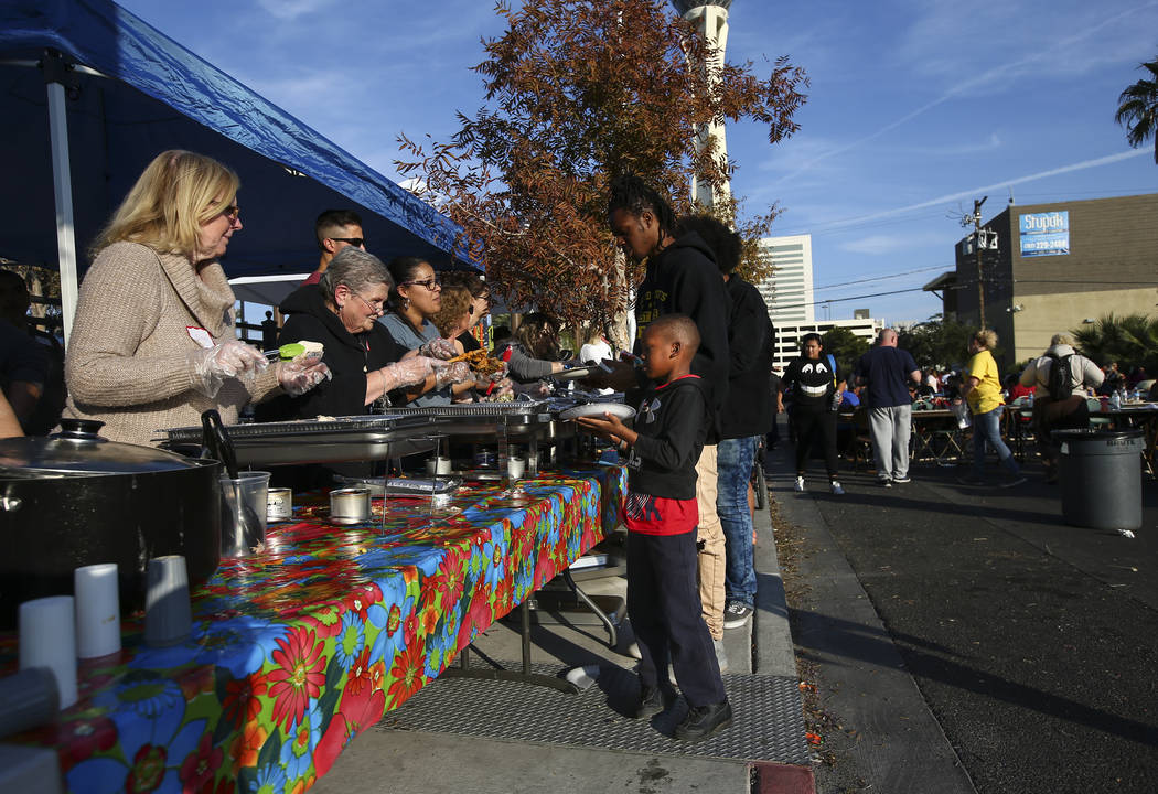 Six-year-old Demetirus Gordon lines up for a warm meal during an annual Thanksgiving outreach event hosted by Casa de Luz and the Las Vegas Metropolitan Police Department's Downtown Area Command a ...