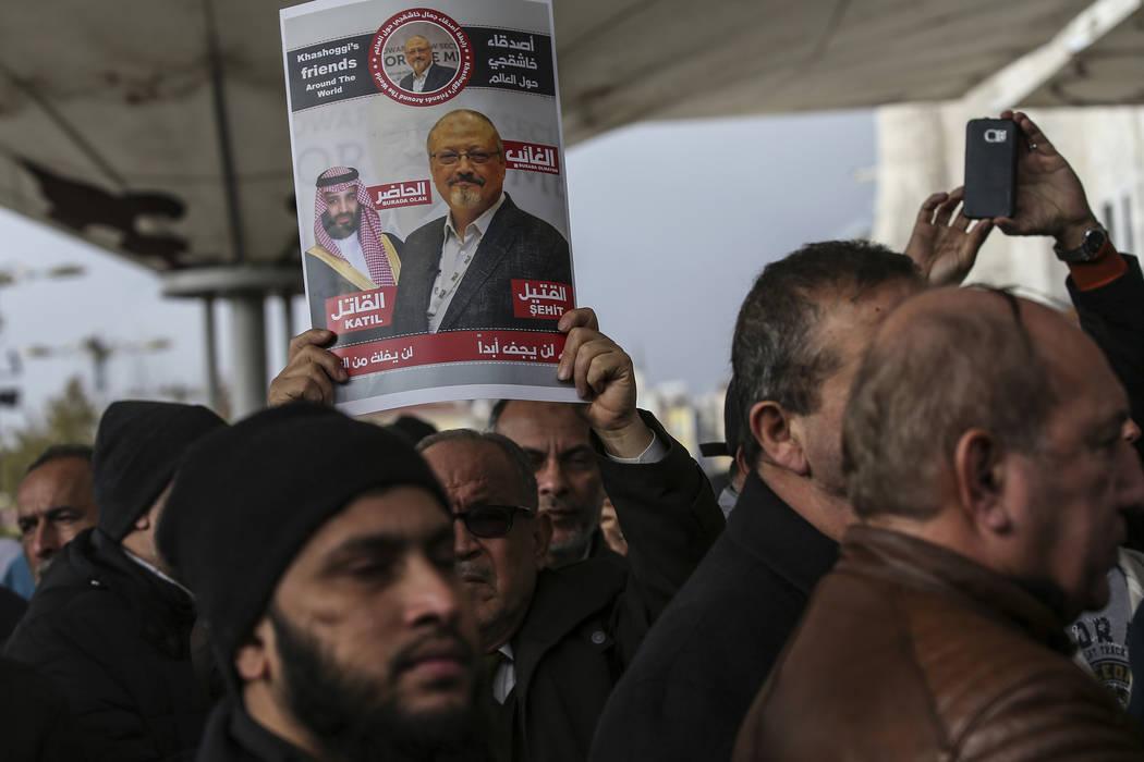 "A man holds a poster showing images of Saudi Crown Prince Muhammed bin Salman and of journalist Jamal Khashoggi, describing the prince as ""assassin"" and Khashoggi as ""martyr"" i ..."