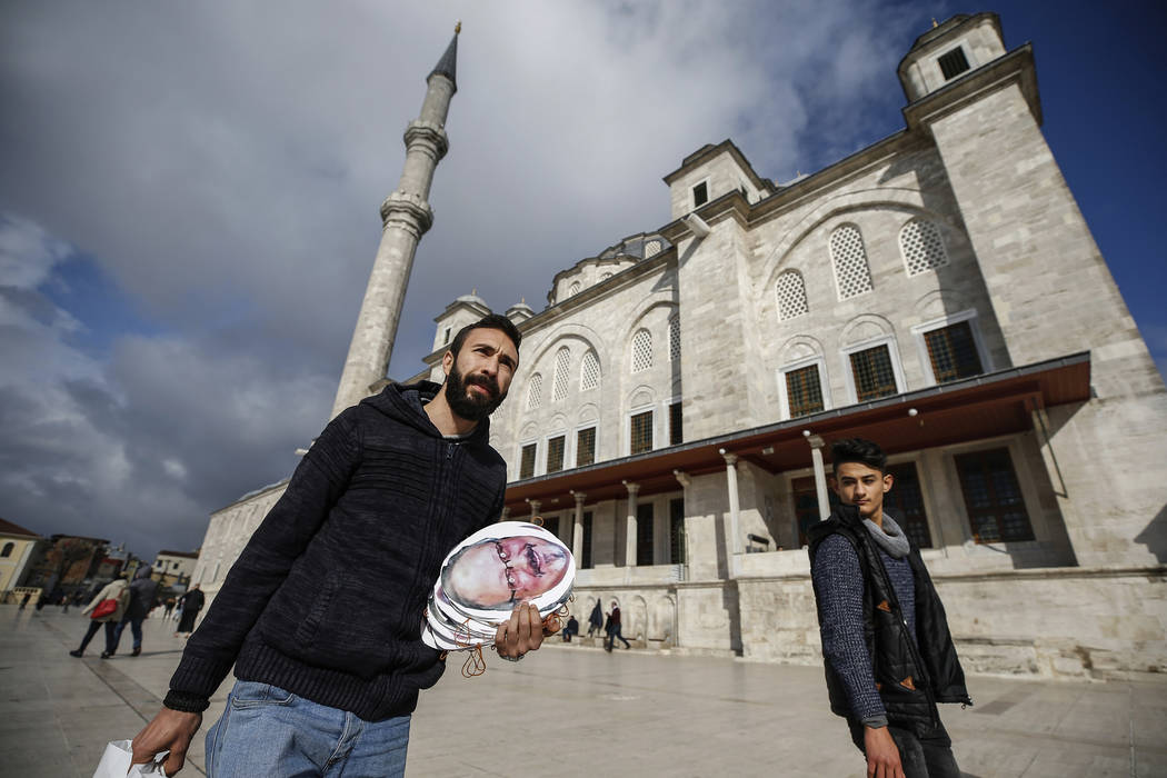 A man holds posters before funeral prayers in absentia for Saudi writer Jamal Khashoggi who was killed last month in the Saudi Arabia consulate, in Istanbul, Friday, Nov. 16, 2018. Turkey's Foreig ...