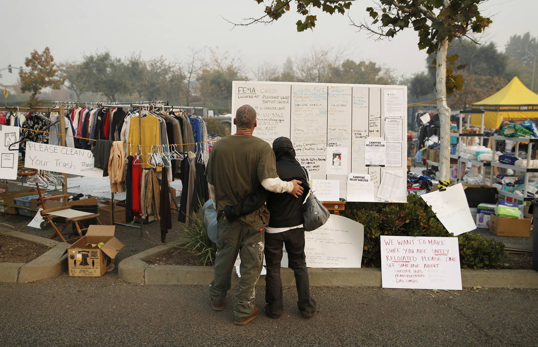 Tera Hickerson, right, and Columbus Holt embrace as they look at a board with information for services at a makeshift encampment outside a Walmart store for people displaced by the Camp Fire, Frid ...
