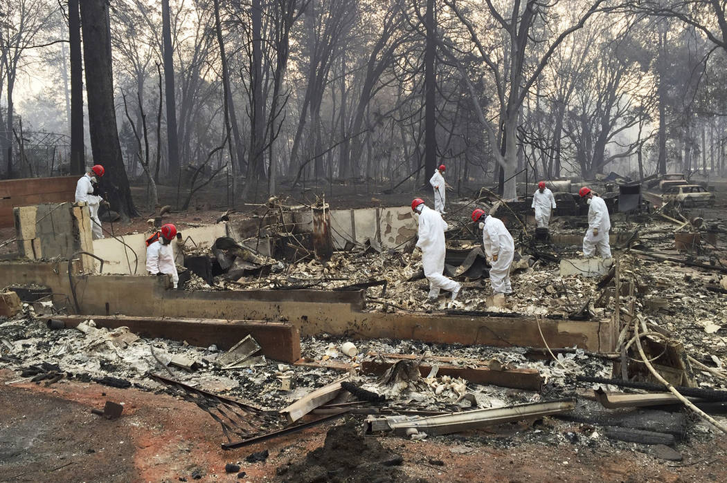 In this Nov. 15, 2018 file photo, volunteer rescue workers search for human remains in the rubble of homes burned in the Camp Fire in Paradise, Calif. (AP Photo/Terry Chea, File)
