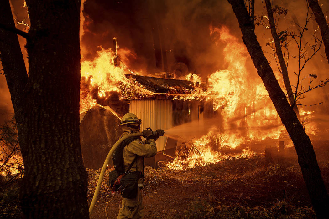 Firefighter Jose Corona sprays water as flames from the Camp Fire consume a home in Magalia, Calif., on Friday, Nov. 9, 2018. (AP Photo/Noah Berger)