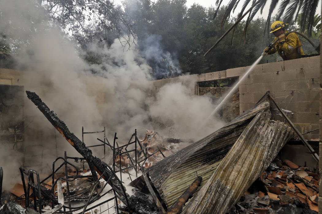 In this Saturday, Nov. 10, 2018, file photo Kevin Brown, with the Los Angeles Fire Dept., hoses down hot spots on a wildfire ravaged home in Malibu, Calif. (AP Photo/Marcio Jose Sanchez, File)