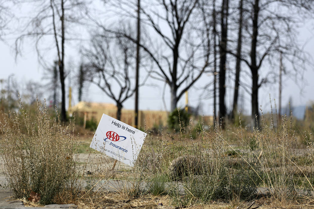 In this Aug. 9, 2018, file a sign from an insurance company sits at the edge of a Santa Rosa, Calif., property that was destroyed in the deadly October 2017 wildfires. (AP Photo/Lorin Eleni Gill, ...