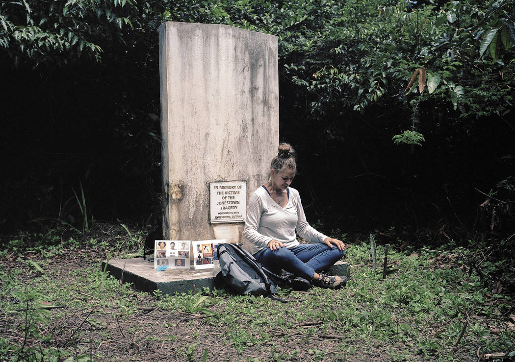 In this March 5, 2018 photo released by Kevin Kunishi, Jordan Vilchez sits at memorial for mass murder and suicide victims at the Jonestown settlement in Guyana. Vilchez returned to Jonestown for ...