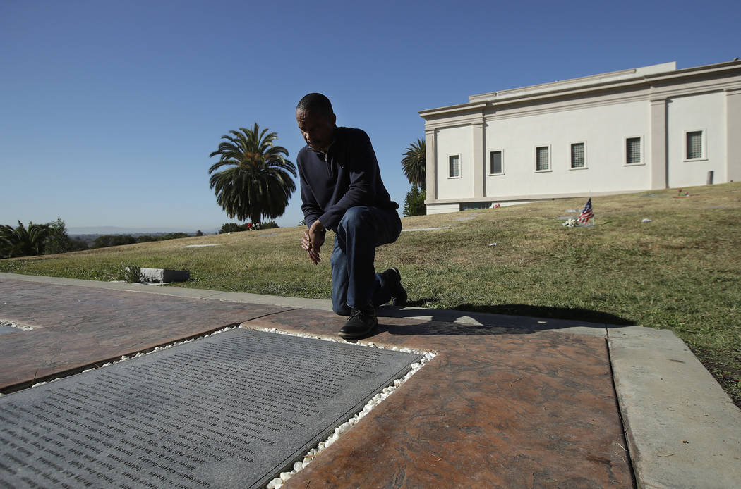 In this Nov. 5, 2018 photo, John Cobb looks at names of family members on the Jonestown Memorial while posing for photos at Evergreen Cemetery in Oakland, Calif. (AP Photo/Jeff Chiu)