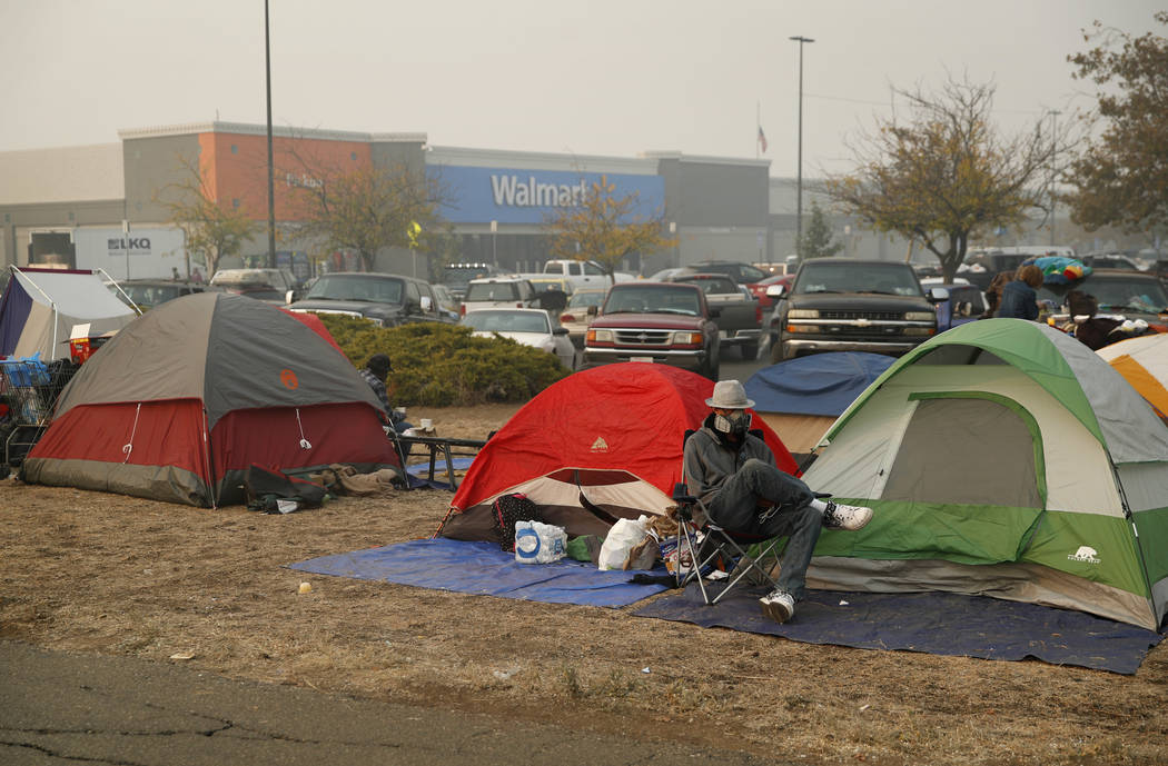 People sit by their tents at a makeshift encampment outside a Walmart store for people displaced by the Camp Fire, Friday, Nov. 16, 2018, in Chico, Calif. (AP Photo/John Locher)