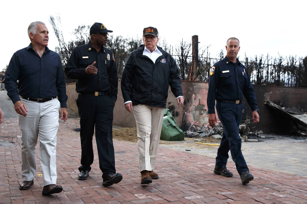 President Donald Trump walks as he visits a neighborhood impacted by the Wolsey Fire, Saturday, Nov. 17, 2018, in Malibu, Calif. (AP Photo/Evan Vucci)
