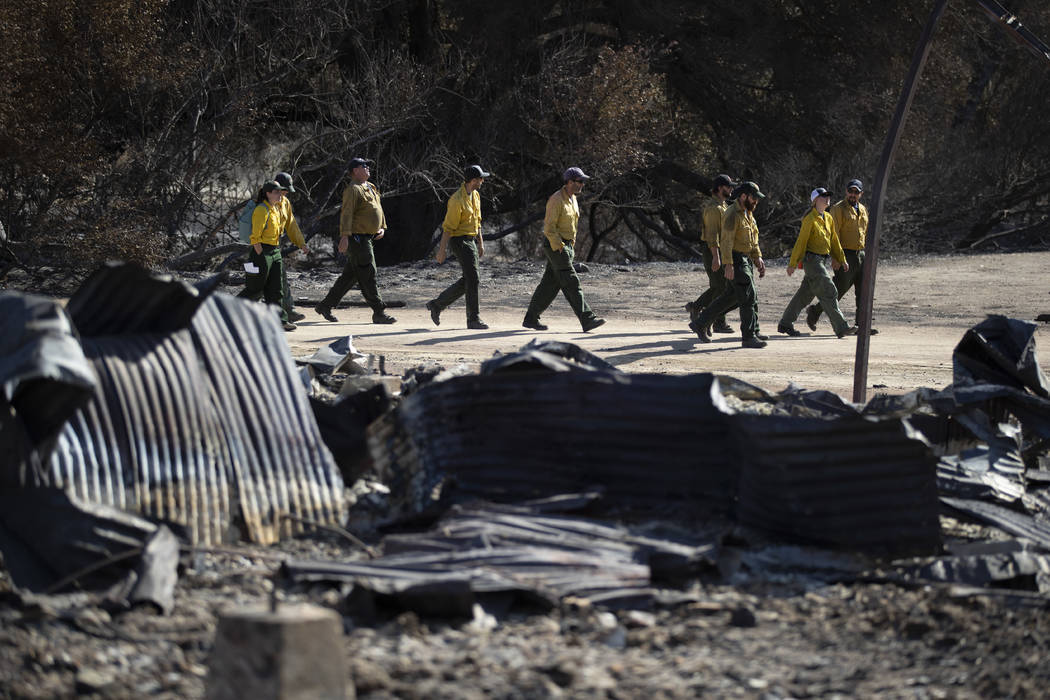 Firefighters walk arrive at decimated Paramount Ranch for a meeting with U.S. Secretary of the Interior Ryan Zinke Thursday, Nov. 15, 2018, in Agoura Hills, Calif. The landmark film location burne ...