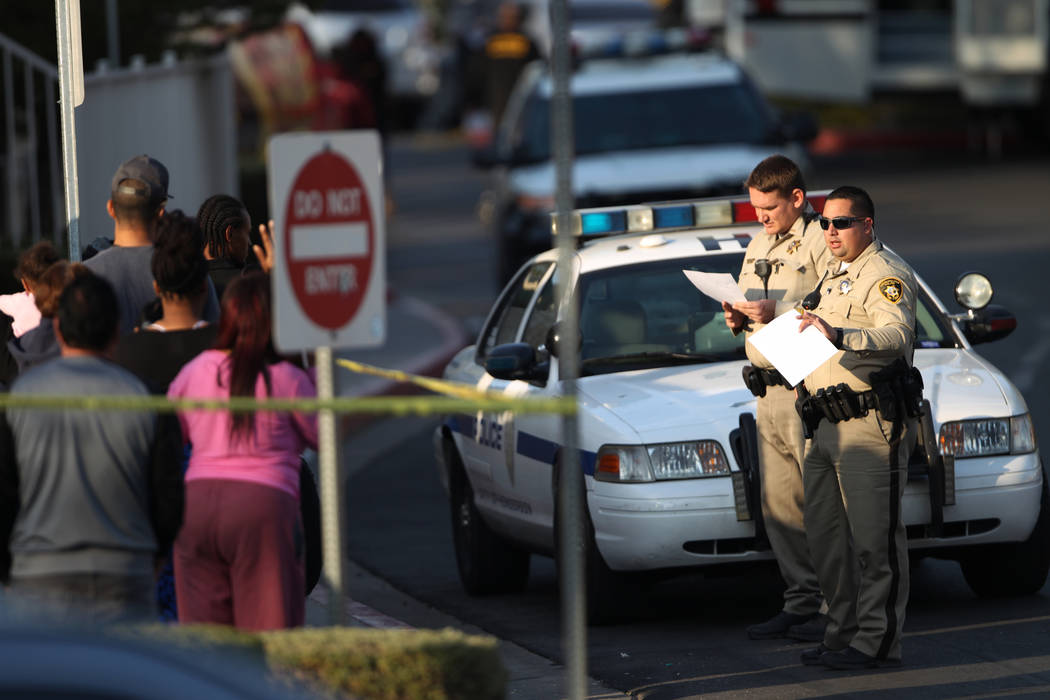 Police talk to people outside of the Apache Pines Apartments, 9500 block of Tropicana Avenue, near Fort Apache Road, where robbery suspects barricaded, in Las Vegas, Saturday, Nov. 17, 2018. Erik ...