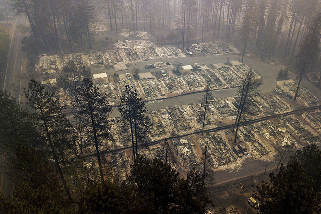 In this Thursday, Nov. 15, 2018 file photo, residences leveled by the wildfire line a neighborhood in Paradise, Calif. (AP Photo/Noah Berger, File)