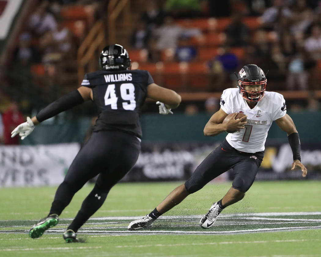UNLV quarterback Armani Rogers (1) slides away from Hawaii defensive lineman Manly Williams (49) during the second quarter of an NCAA college football game, Saturday, Nov. 17, 2018, in Honolulu. ( ...