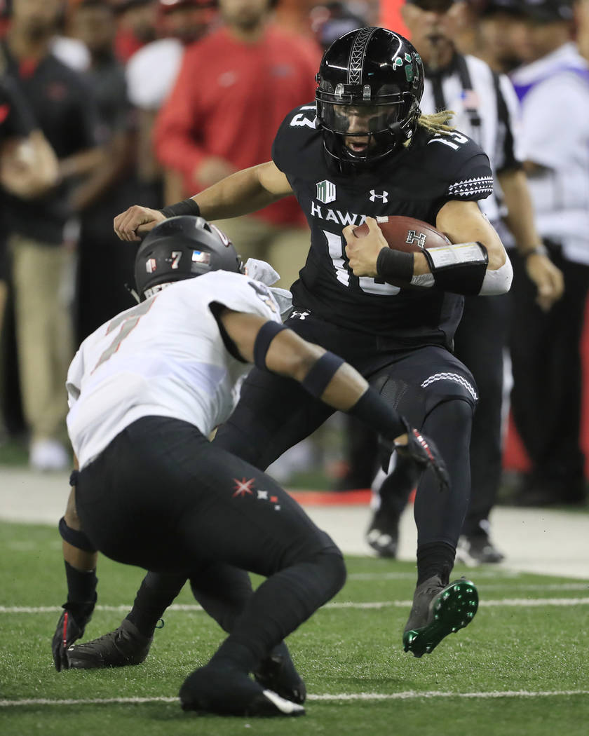 Hawaii quarterback Cole McDonald (13) tries to leap over UNLV defensive back Evan Austrie (17) during the first quarter of an NCAA college football game, Saturday, Nov. 17, 2018, in Honolulu. (AP ...