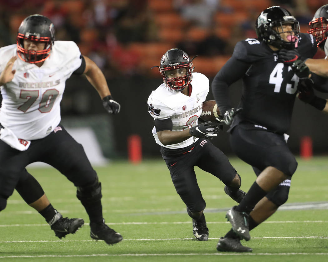 UNLV running back Lexington Thomas (3) breaks through the Hawaii defensive line during the first quarter of an NCAA college football game, Saturday, Nov. 17, 2018, in Honolulu. (AP Photo/Marco Garcia)