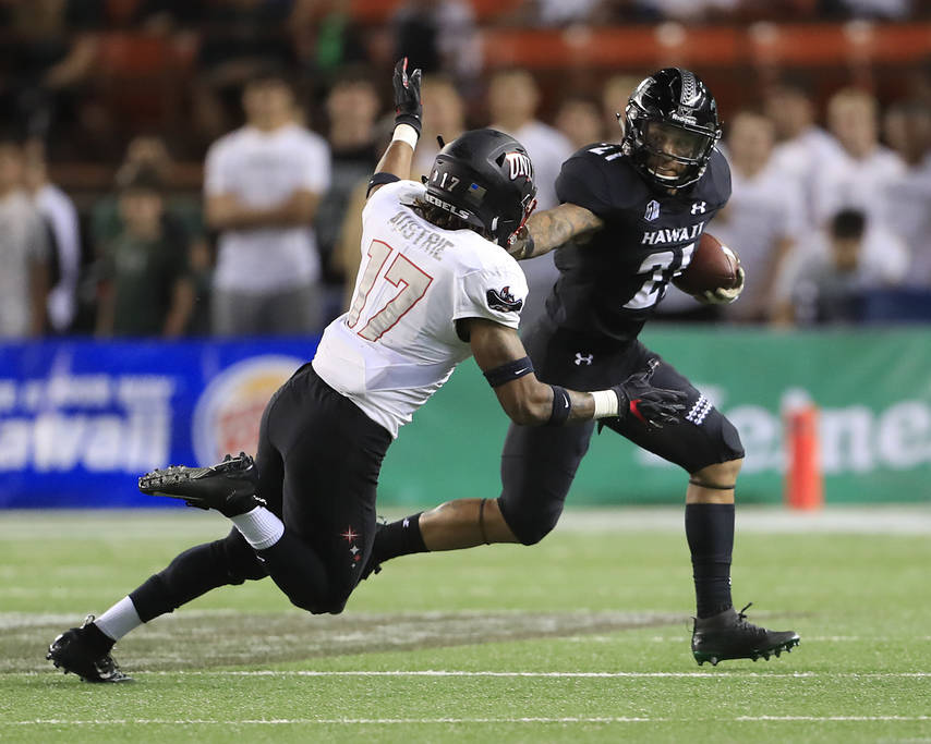 Hawaii running back Fred Holly III (21) stiff arms UNLV defensive back Evan Austrie (17) during the first quarter of an NCAA college football game, Saturday, Nov. 17, 2018, in Honolulu. (AP Photo/ ...