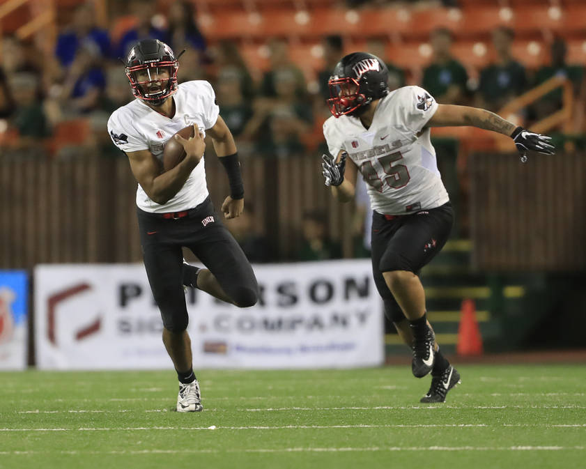 As UNLV tight end Giovanni Fauolo (45) runs with him, UNLV quarterback Armani Rogers (1) gains yards against Hawaii during the third quarter of an NCAA college football game, Saturday, Nov. 17, 20 ...