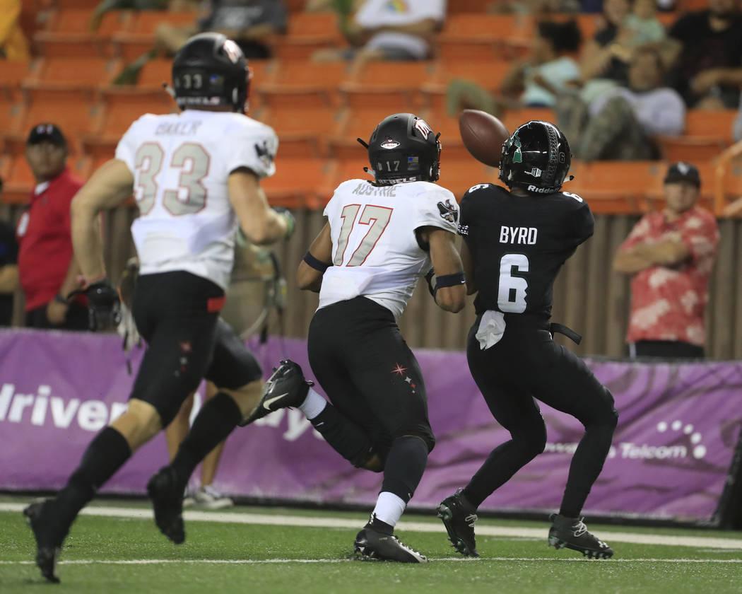 While being guarded by UNLV defensive back Evan Austrie (17), Hawaii wide receiver Cedric Byrd (6) pulls in a catch during the third quarter of an NCAA college football game, Saturday, Nov. 17, 20 ...