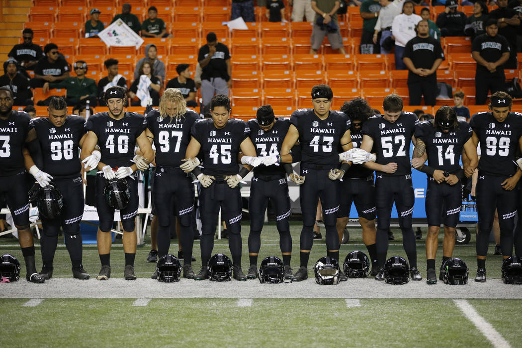 Hawaii football players lock arms in memory of former Hawaii football player Vince Manuwai before the start of an NCAA college football game against UNLV, Saturday, Nov. 17, 2018 in Honolulu. Manu ...