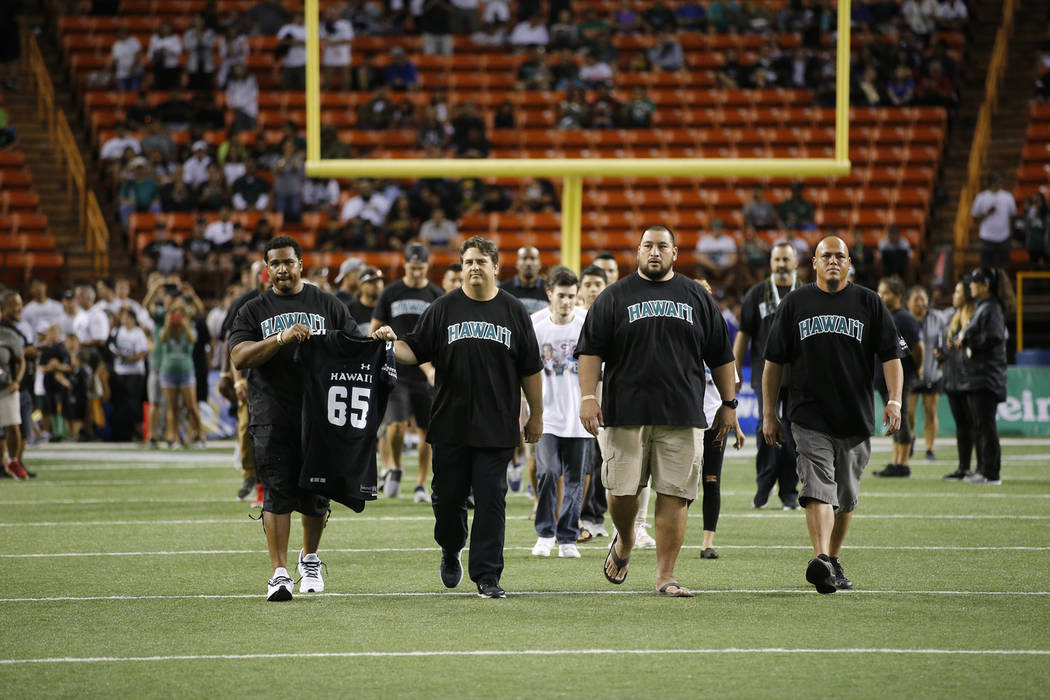 While holding the jersey of former Hawaii football player Vince Manuwai, former Hawaii football players, staff, and alumni walk onto the field in memory of Manuwai before the start of an NCAA coll ...