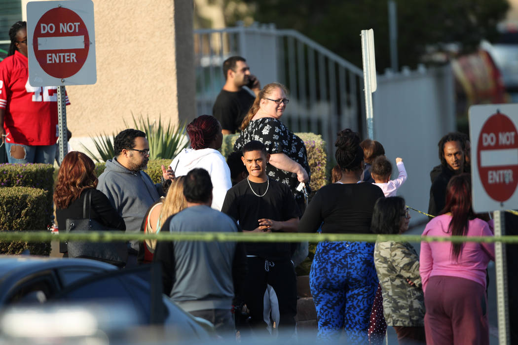 People wait outside of the Apache Pines Apartments, 9500 block of Tropicana Avenue, near Fort Apache Road, where robbery suspects barricaded, in Las Vegas, Saturday, Nov. 17, 2018. Erik Verduzco L ...