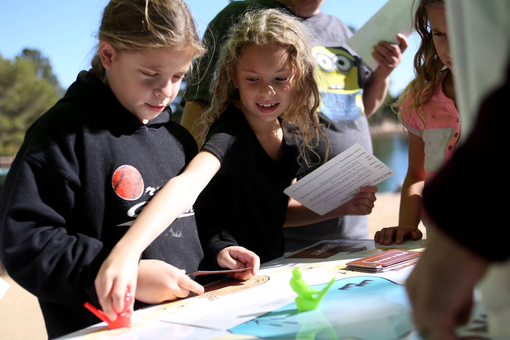 Jayden Hallmark, 9, from left, and her triplet sister Jenna Hallmark, 9, play a game to learn about birds at Migratory Bird Day at Sunset Park in Las Vegas, Sunday, Nov. 18, 2018. Different organi ...