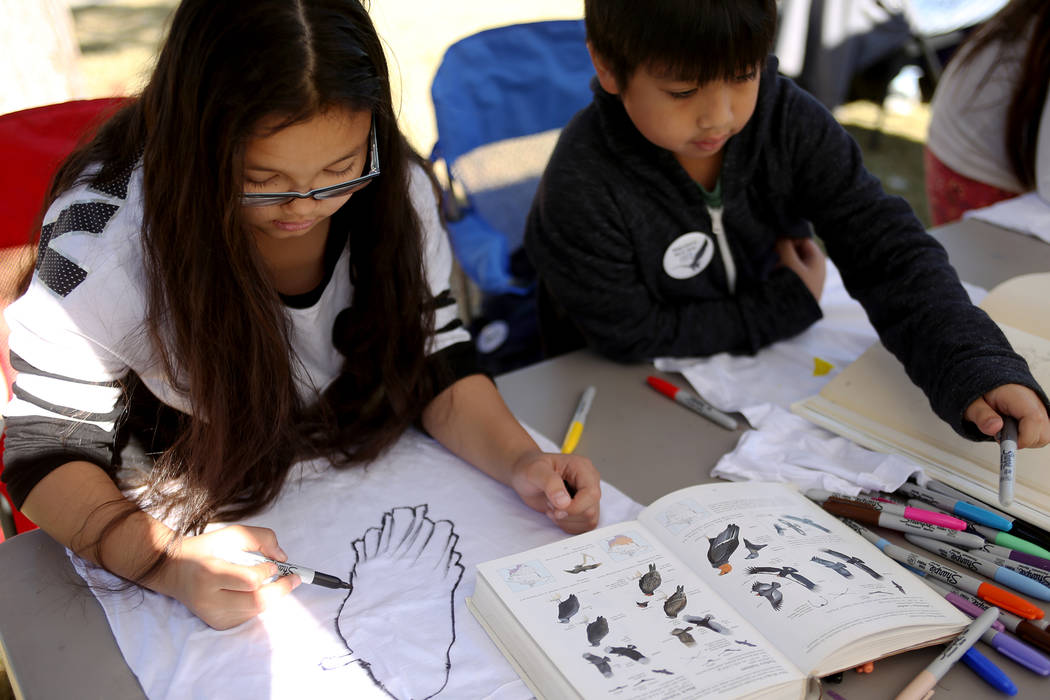 Layna Umipig, 9, left, and her brother Liam Umipig, 8, draw birds on t-shirts at Migratory Bird Day at Sunset Park in Las Vegas, Sunday, Nov. 18, 2018. Different organizations offered activities f ...