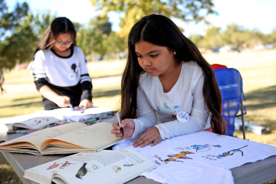 Zelliyah Nato, 7, draws birds on a t-shirt at a booth at Migratory Bird Day at Sunset Park in Las Vegas, Sunday, Nov. 18, 2018. Different organizations offered activities for kids and adults to le ...