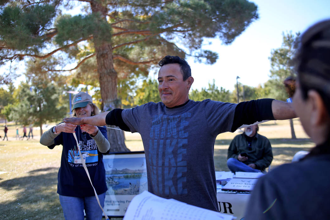 Jane Taylor checks what would be the wing span of Rupert Herrera while his family watches at a booth at Migratory Bird Day at Sunset Park in Las Vegas, Sunday, Nov. 18, 2018. Different organizatio ...