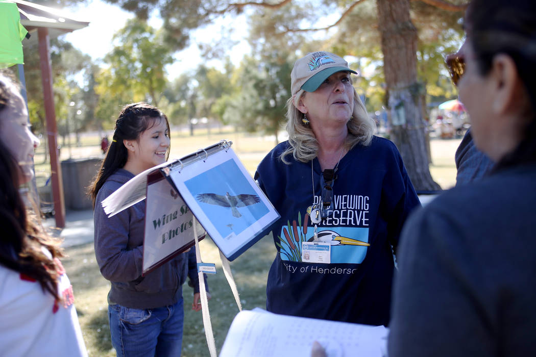 Jane Taylor shows the Herrera family that Rupert Herrera's arm span would be an Osprey at a booth at Migratory Bird Day at Sunset Park in Las Vegas, Sunday, Nov. 18, 2018. Different organizations ...
