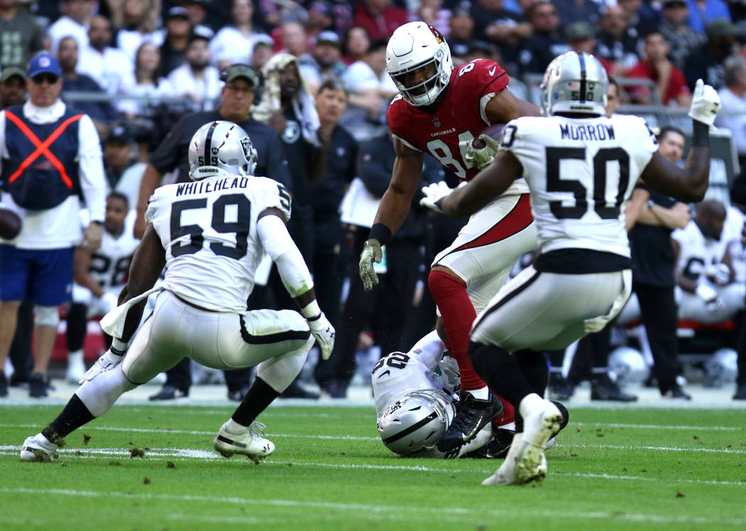 Arizona Cardinals tight end Jermaine Gresham (84) breaks a tackle from Oakland Raiders defensive back Leon Hall (29) as outside linebacker Tahir Whitehead (59) and linebacker Nicholas Morrow (50) ...