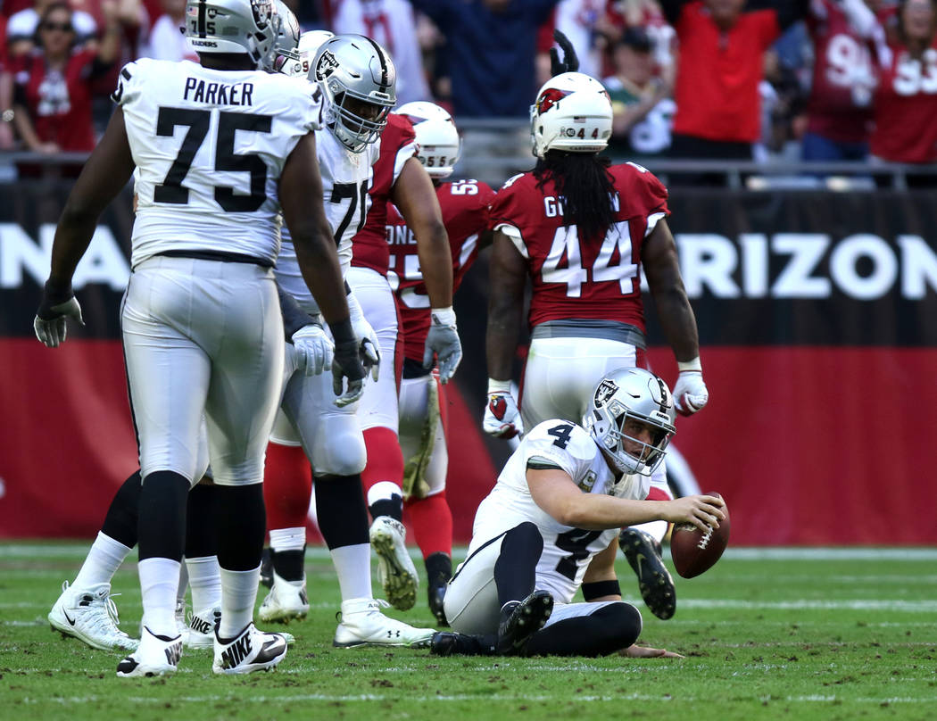Oakland Raiders quarterback Derek Carr (4) gets up after being sacked by Arizona Cardinals defensive end Chandler Jones (55) during the first half of an NFL game in Glendale, Ariz., Sunday, Nov. 1 ...
