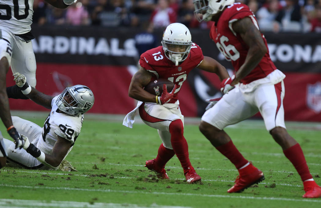 Arizona Cardinals wide receiver Christian Kirk (13) breaks free of a tackle by Oakland Raiders defensive end Arden Key (99) on his way to scoring a touchdown during the first half of an NFL game i ...