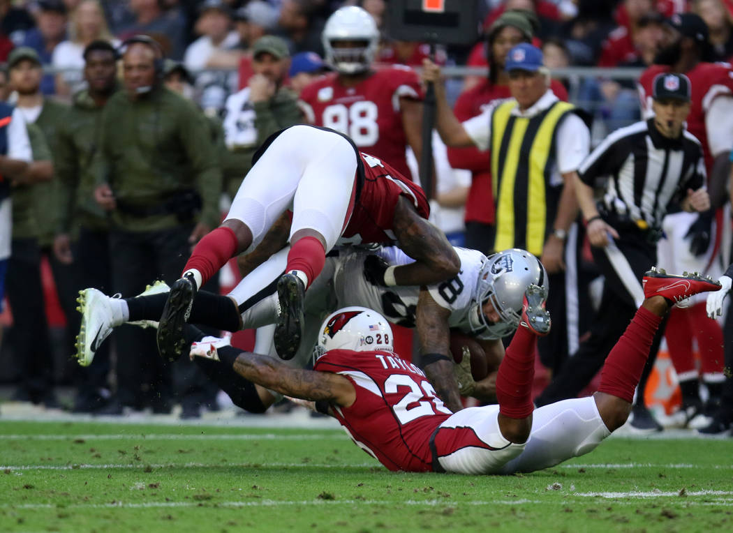 Oakland Raiders running back Doug Martin (28) leaps for more yards as Arizona Cardinals cornerback Jamar Taylor (28) and defensive end Markus Golden (44) tackle him during the first half of an NF ...