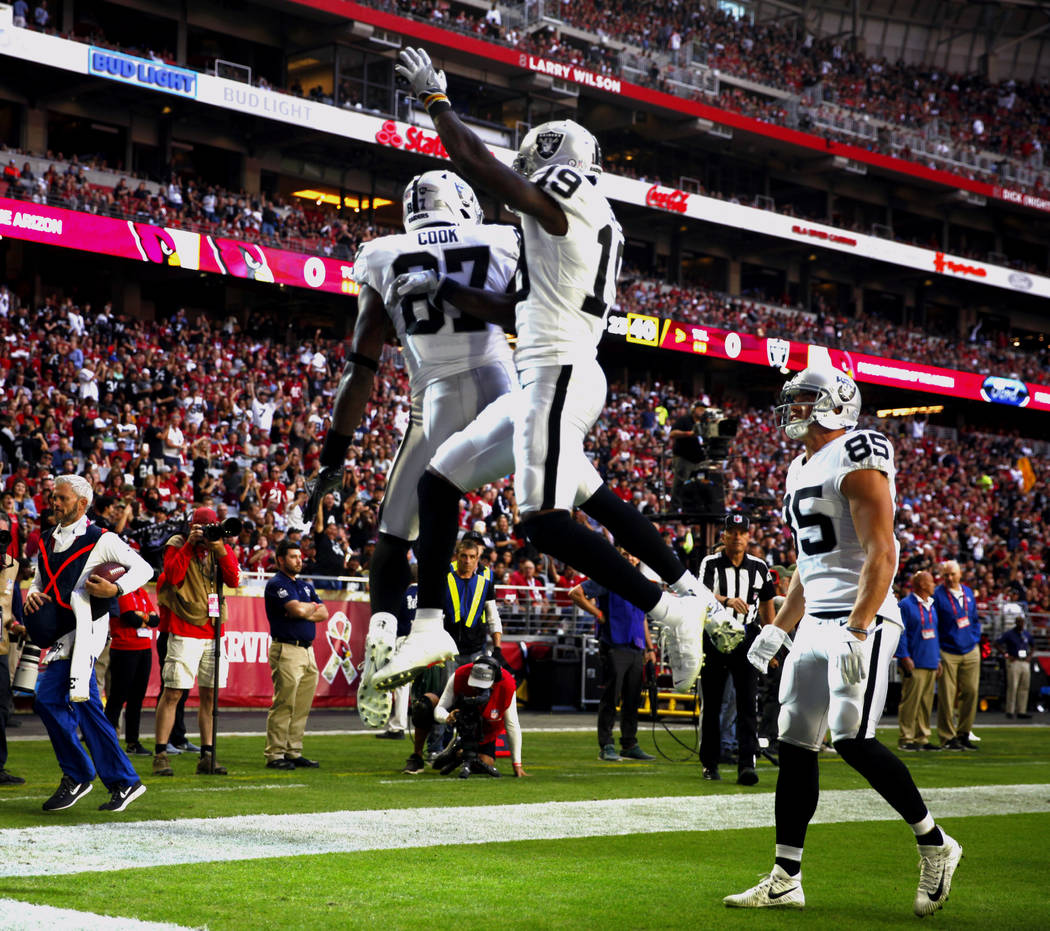 Oakland Raiders tight end Jared Cook (87) celebrates his touchdown by leaping in the air with wide receiver Brandon LaFell (19) as tight end Derek Carrier (85) looks on during the first half of an ...