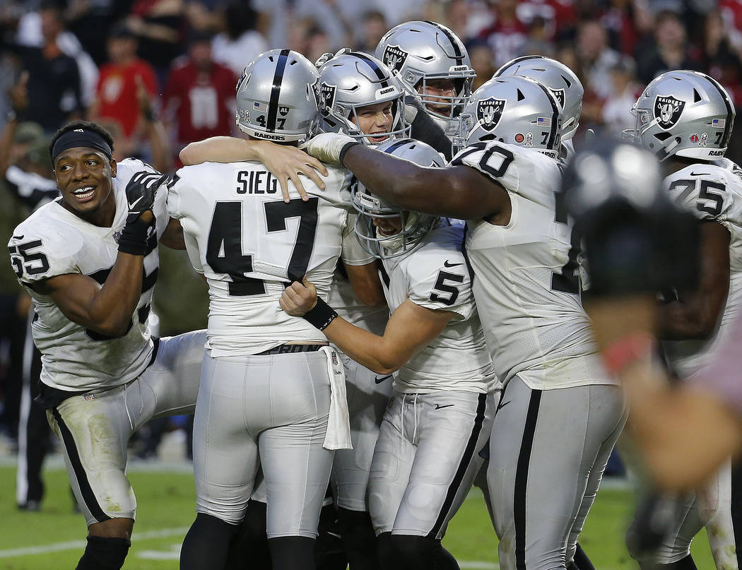The Oakland Raiders celebrate as time expires during the second half of an NFL football game against the Arizona Cardinals, Sunday, Nov. 18, 2018, in Glendale, Ariz. The Raiders won 23-21. (AP Pho ...