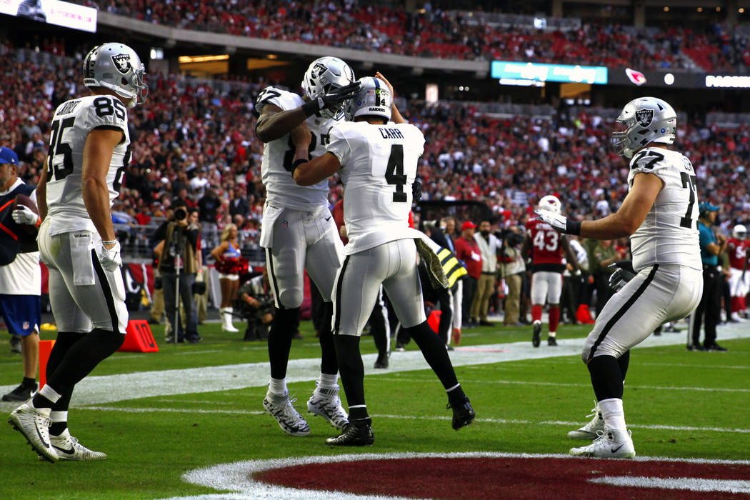 Oakland Raiders quarterback Derek Carr (4) celebrates his touchdown thrown to tight end Jared Cook (87) as tight end Derek Carrier (85) and offensive tackle Kolton Miller (77) look on during the f ...