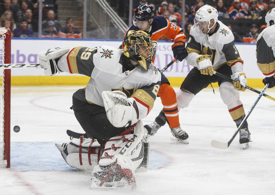 Vegas Golden Knights goalie Marc-Andre Fleury (29) makes a save as Brayden McNabb (3) and Edmonton Oilers' Alex Chiasson (39) look for a rebound during the second period of an NHL hockey game Sund ...
