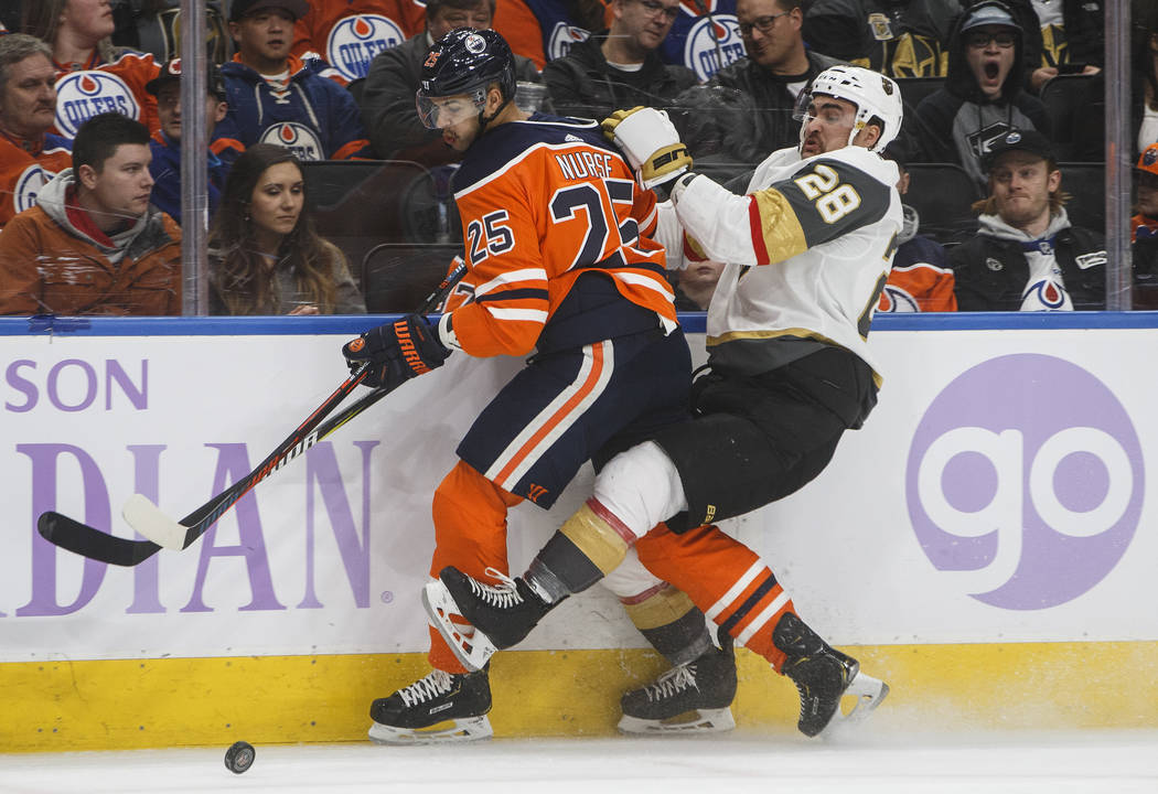Vegas Golden Knights' William Carrier (28) is checked by Edmonton Oilers' Darnell Nurse (25) during first period NHL hockey action in Edmonton, Alberta, on Sunday Nov. 18, 2018. (Jason Franson/The ...
