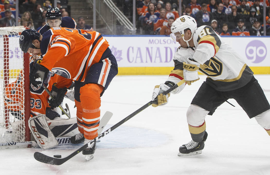 Vegas Golden Knights' Jonathan Marchessault (81) is stopped by Edmonton Oilers goalie Cam Talbot (33) as Kyle Brodziak (28) tries to pick up the rebound during the first period of an NHL hockey ga ...