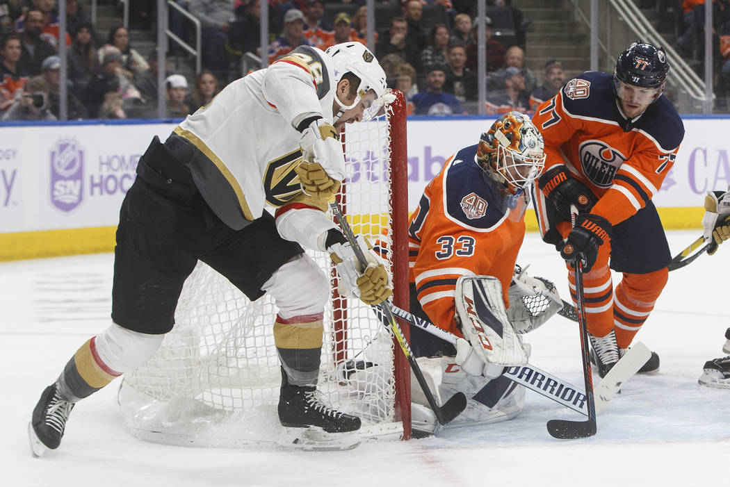 Vegas Golden Knights' William Carrier (28) is stopped by Edmonton Oilers goalie Cam Talbot (33) as Oscar Klefbom (77) defends during the first period of an NHL hockey game Sunday, Nov. 18, 2018, i ...